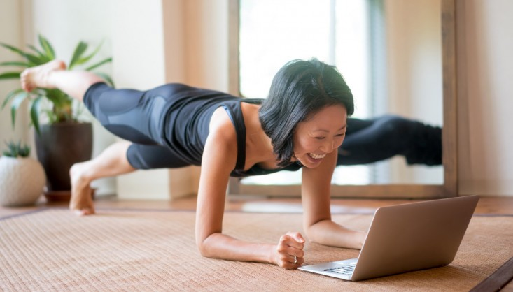 Asian woman exercising at home following a fitness video online